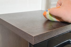 DUSTING WITH CLOTH TO MAKE WOODEN FURNITURE MORE DURABLE