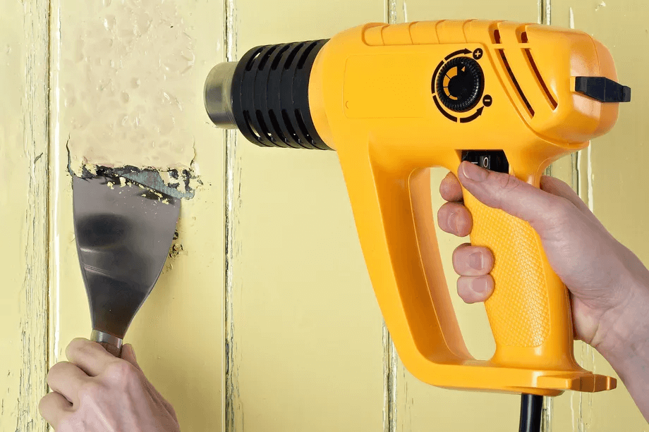 A HEAT GUN TO REMOVE PAINT FROM WOOD SURFACE